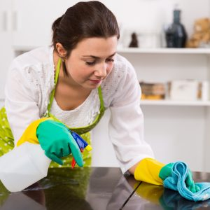 Attentive girl cleans table with help of modern cleaning agents